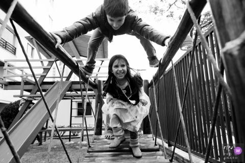 Un garçon et une fille en tenue de soirée jouent ensemble sur un pont dans cette photo enregistrée par un photographe de famille de style documentaire primé à Sao Paulo.