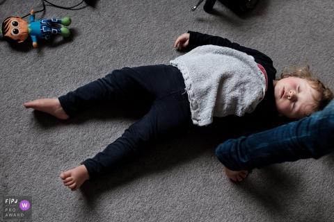 Une petite fille pose allongée sur le sol sur cette photo d'un photographe de famille primé de Noord Barbant, aux Pays-Bas.