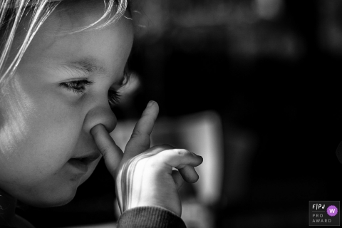 A little girl picks her nose without shame in this photograph created by a Noord Barbant, Netherlands family photojournalist.