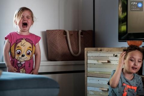 Un garçon porte la main à son oreille pendant que sa sœur pleure derrière lui dans cette image de famille de style documentaire enregistrée par un photographe de Noord Barbant, aux Pays-Bas.