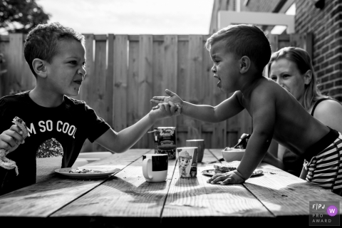 Two little boys have an argument across a picnic table in this documentary-style family photo captured by a Noord Holland, Netherlands photographer.