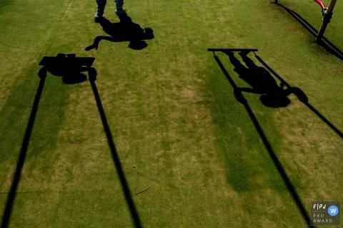 Les ombres de deux enfants en balançoire sont visibles sur l'herbe sur cette photo réalisée par un photographe de famille documentaire de Noord Holland, aux Pays-Bas.