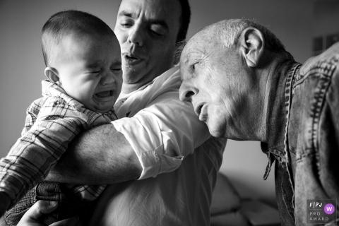 Un père et un grand-père tentent de réconforter un petit garçon en pleurs dans cette photo récompensée par la photo de famille par un photographe documentaire de famille du Rio Grande do Sul, au Brésil.