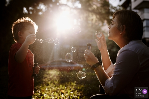 A mother blows bubbles outside with her son in this FPJA award-winning image captured by a Rio Grande do Sul, Brazil family photographer.
