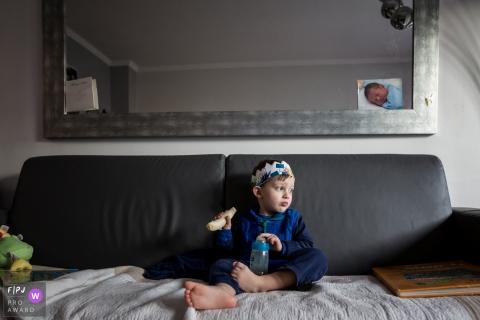 Un garçon assis sur un canapé tenant une bouteille d'eau et une courge jaune dans cette image capturée par un photojournaliste de la famille France.