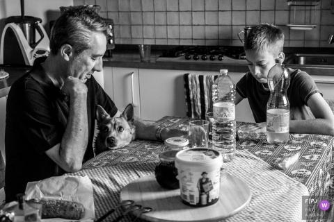 Un chien demande de la nourriture pendant que son père et son fils sont assis à la table de la cuisine sur cette photo réalisée par un photographe de famille primé à Modène.