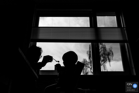 The silhouette of a father feeding his son can be seen in this photograph created by a Modena family photojournalist.