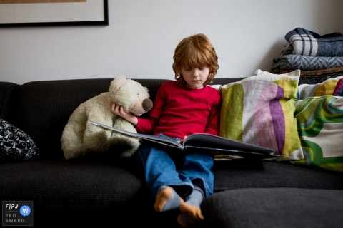 Un petit garçon caresse son ours en peluche pendant qu'il lit un livre dans cette image de famille de style documentaire enregistrée par un photographe d'Amsterdam.
