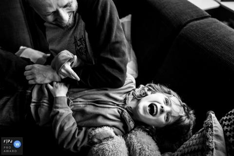 Un petit garçon rigole pendant que son père le chatouille dans le cadre de ce concours récompensant une photo de la famille Photojournalist Association, créé par un photographe de famille d'Amsterdam.
