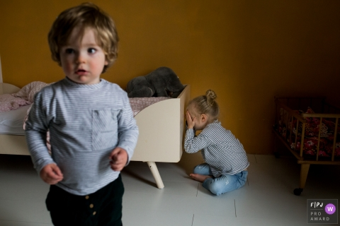 Un garçon debout dans une chambre à coucher tandis que sa sœur est assise contre son lit, ses mains couvrant ses yeux, dans cette image primée du FPJA par un photographe de famille d'Amsterdam.
