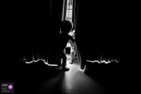 Deux jeunes frères et sœurs jouent à travers un rideau dans cette photo de famille au style documentaire prise par un photographe d'Amsterdam.