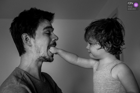 A little boy puts his fist in his father's mouth in this family picture by an Amsterdam photographer.