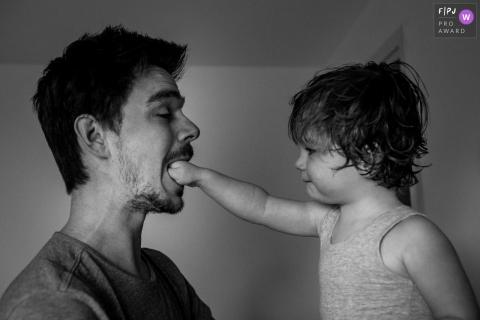 Un petit garçon met son poing dans la bouche de son père dans cette photo de famille réalisée par un photographe d'Amsterdam.