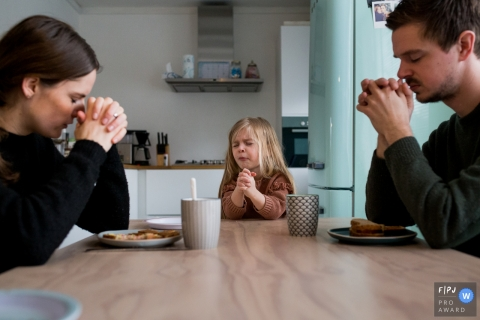 A girl makes a face while she and her parents pray before their meal in this photograph by an Amsterdam documentary family photographer.