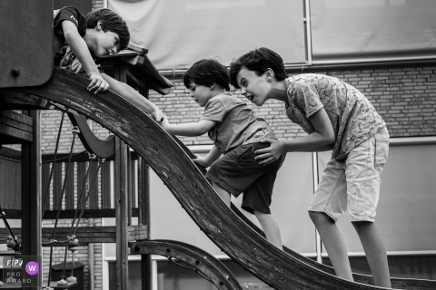 A boy helps his little brother climb up a slide in this Family Photojournalist Association awarded photo by a Zwolle, Overijssel documentary family photographer.