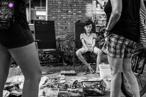 A little boy sits outside running a yard sale in this FPJA award-winning image captured by a Zwolle, Overijssel family photographer.