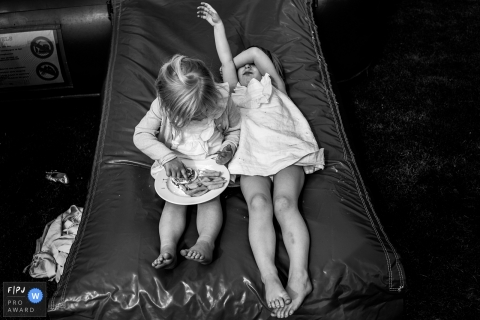 A little girl lays next to her sister who eats a plate of food in this award-winning photo by a Zwolle, Overijssel family photographer.
