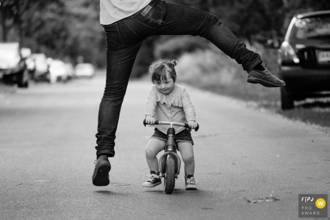 A father playfully leaps over his daughter who rides a small bike in this photo recorded by a Berlin, Germany award-winning, documentary-style family photographer.