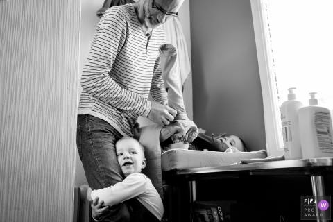 Un garçon tient la jambe de son père pendant qu'il habille son petit frère sur cette image capturée par un photojournaliste de la famille nantaise, Loire-Atlantique.