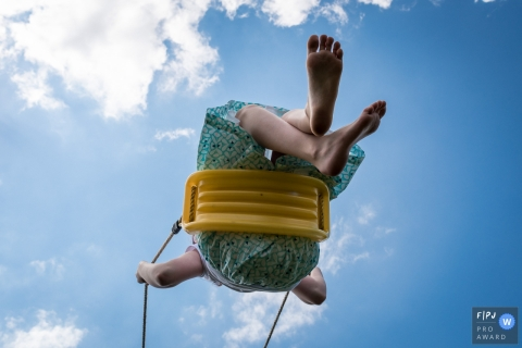 A little girl soars on a yellow swing in this documentary-style family image recorded by a Nantes, Loire-Atlantique photographer.