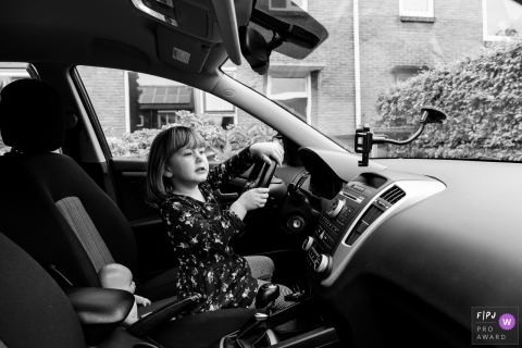 Une petite fille fait semblant de conduire une voiture dans le cadre de ce concours de l'association de photojournalistes de famille récompensé par une photo réalisée par un photographe de famille de Gelderland, Pays-Bas.