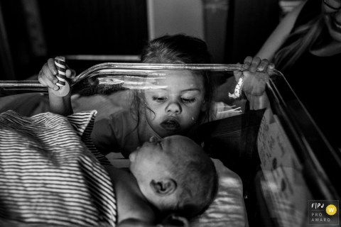 A little girl presses her nose up against a clear bin to see her newborn sibling in the hospital in this black and white photo by a South Bend, IN birth photographer.