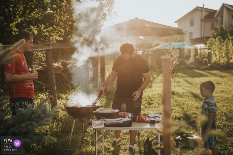 A boy watches his father cooking over the grill outside in this family picture by a Cluj photographer.