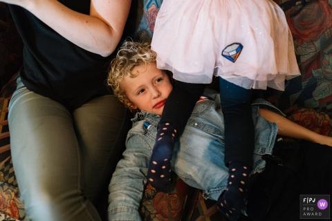 Un garçon est allongé sur le canapé et fait une grimace alors que sa soeur est agenouillée contre la poitrine dans cette photo récompensée par une photo photo de famille par un photographe de famille documentaire d'Utrecht, Pays-Bas.