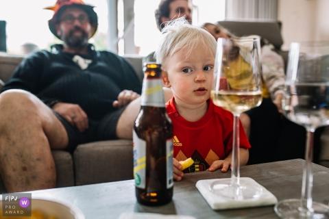 Un petit garçon regarde une bouteille de bière avec curiosité sur cette image créée par un photographe de famille d'Utrecht, Pays-Bas.