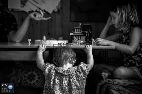 Une petite fille s'accroche à une table où sa mère et sa soeur sont assises sur cette photo enregistrée par un photographe de famille de style documentaire primé à Copenhague, au Danemark.