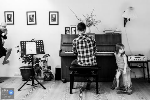Une petite fille se tient à côté de son père pendant qu'il joue du piano sur cette photo créée par un photojournaliste de la famille de Copenhague, au Danemark.