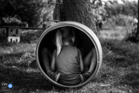 Deux enfants jouent dans un tonneau à l'extérieur dans cette image familiale de style documentaire, enregistrée par un photographe de Copenhague, au Danemark.