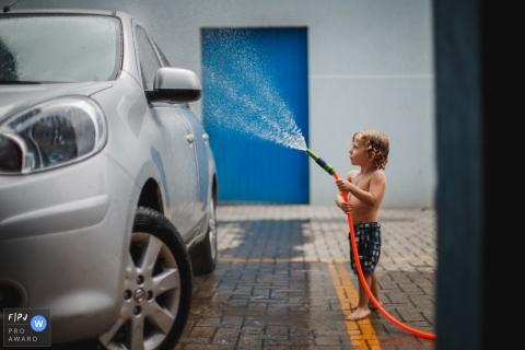 Un petit garçon arrose une voiture dans cette photo primée d'un prix FPJA réalisée par un photographe de famille de Santa Catarina, au Brésil.