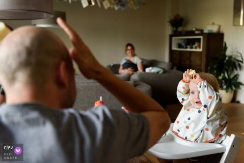 Un bébé garçon imite son père qui lève la main vers la tête dans cette photo de famille au style documentaire prise par un photographe de Zuid Holland, aux Pays-Bas.