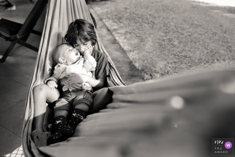 A boy holds his baby brother in his lap while they sit in a hammock in this family picture by a Macae, Rio de Janeiro photographer.