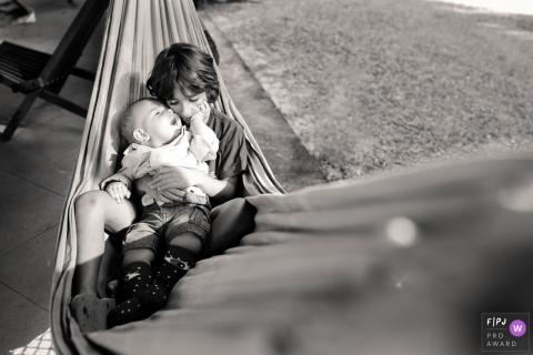 Un garçon tient son petit frère sur ses genoux pendant qu'ils sont assis dans un hamac dans cette photo de famille réalisée par un photographe de Macae, à Rio de Janeiro.