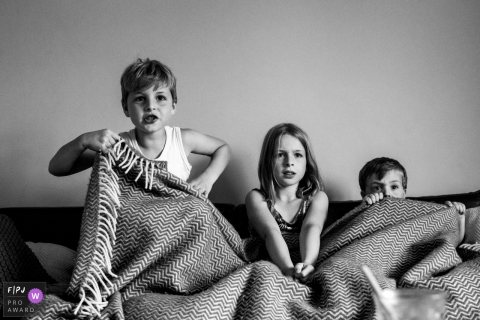 Three siblings share a blanket on a couch while they watch TV in this FPJA award-winning image captured by a Breda, Noord Barbant family photographer.