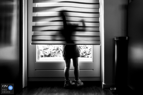 A little girl looks out a window from beneath the blinds in this award-winning photo by a Breda, Noord Barbant family photographer.