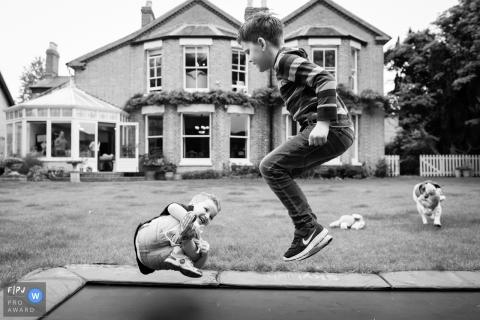 Deux jeunes garçons jouent sur un trampoline à l'extérieur dans cette image créée par un photographe de famille du Cambridgeshire, en Angleterre.