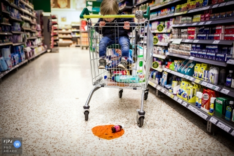 A little boy in a grocery cart looks down at a broken bottle in this photo recorded by a Bath, Somerset award-winning, documentary-style family photographer.