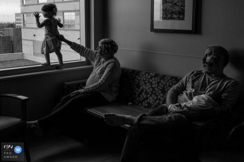 Une mère s'accroche à la robe de sa fille qui se tient debout sur un rebord de fenêtre sur cette photo prise par un photojournaliste de la famille de Boulder, CO.