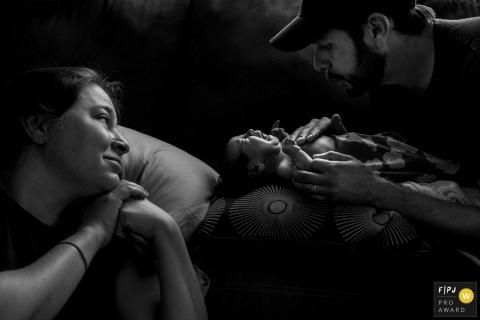 Une femme regarde pendant que son mari tente de calmer leur bébé en pleurs sur le canapé, sur cette photo prise par un photographe de famille primé à Boulder, CO.