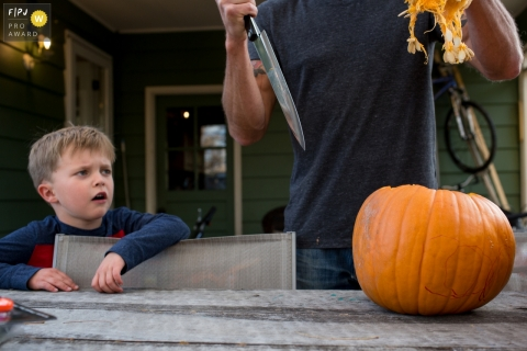 A little boy looks concerned as his father uses a large knife to clean out a pumpkin in this photograph created by a Boulder, CO family photojournalist.
