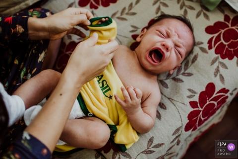 Un petit garçon pleure pendant que sa mère tente de l'habiller de cette image de famille de style documentaire enregistrée par un photographe de Rio de Janeiro, au Brésil.