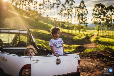 Two children look out the back of a truck bed in this documentary-style family photo captured by a Sao Paulo, Brazil photographer.