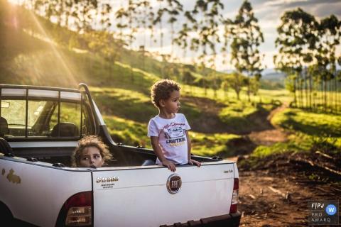 Deux enfants regardent l'arrière d'un camion dans cette photo de famille de style documentaire, réalisée par un photographe de Sao Paulo, au Brésil.