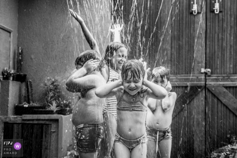 Four children rinse off beneath streams of water in this family picture by a Sao Paulo, Brazil photographer.