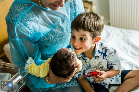 A little boy is excited to meet his new sibling for the first time in the hospital in this photo by a Cluj documentary birth photographer.