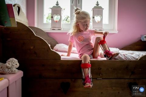 Une petite fille met ses jambières roses dans sa chambre rose dans cette image primée du FPJA, capturée par un photographe de famille à Utrecht, aux Pays-Bas.
