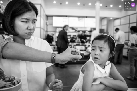 Une petite fille regarde avec inquiétude un morceau de nourriture que son père lui tend avec cette image créée par un photographe de famille de Surrey, en Angleterre.